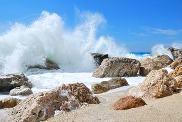 Big sea wave splashing over the shore rocks with a sea spray
