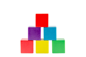 Wooden colored building pyramid of cubes toys isolated on white