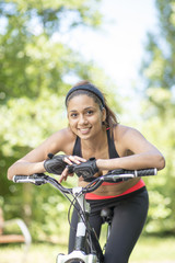 Portrait of beautiful smiling latin athletic woman with bike, ou