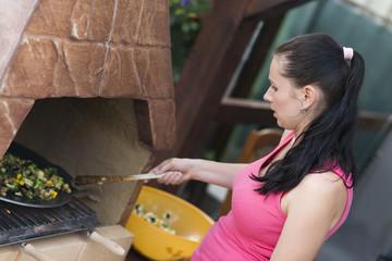 Femme en vacances préparant les légumes grillés