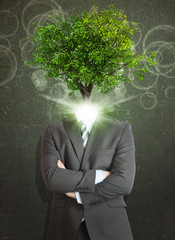 Businessman stand with green tree instead his head