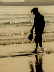 Anciano caminando por la orilla de la playa