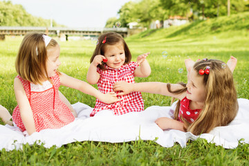 Three little sisters in red dresses having picnic outdoors