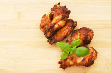 Deep dried chicken wings on a bamboo cutting board with basil le