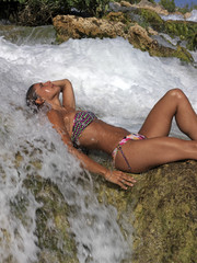 Young woman in bikini bathing under a waterfall...