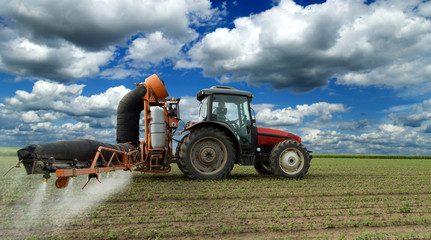 Tractor spraying soybean crops field with sprayer, pesticides