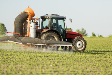 Tractor spraying soybean crops field with sprayer