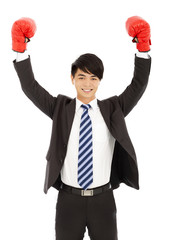 smiling businessman raises hands with gloves