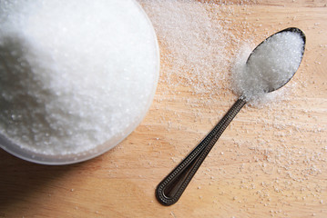sugar in a cup on wood table background