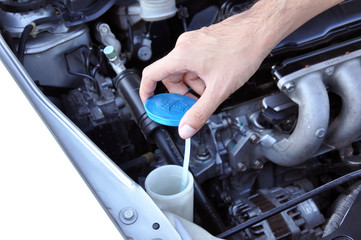 Hand opening car windscreen washer tank checking water level
