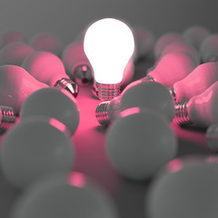 growing light bulb standing out from the unlit incandescent bulb