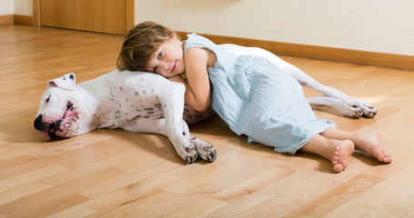 little smiling girl on the floor with dog