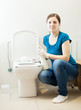 woman cleaning toilet brush with sponge