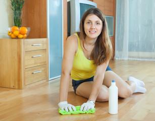 Girl rubbing wooden floor with  cleanser