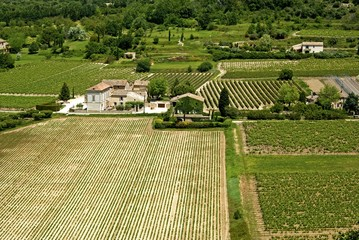 Countryside in France with vineyards and buildings.