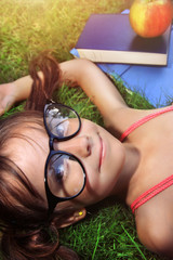 Back to school - happy girl with glasses on the grass