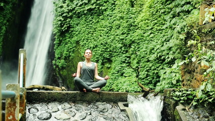 Young woman meditating by amazing waterfall in Bali, Indonesia