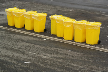 a Row of yellow garbage collectors prepared for an event