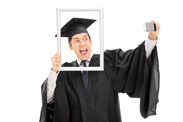 Graduate taking selfie behind a picture frame