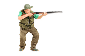Mature hunter aiming at something with a gun