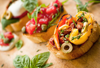 Bruschettas with mozzarella and vegetables on the wooden table