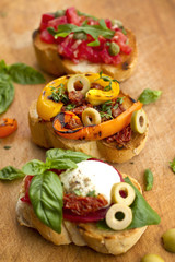 Bruschettas with mozzarella, vegetables and herbs