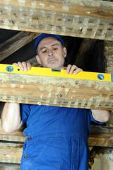 Handwerker mit Wasserwaage im Dachstuhl