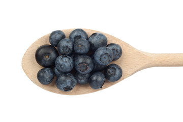 Blueberries on wooden spoon isolated on white