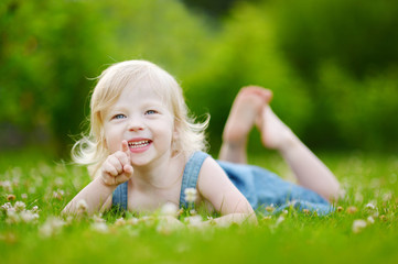 Cute little toddler girl laying in the grass