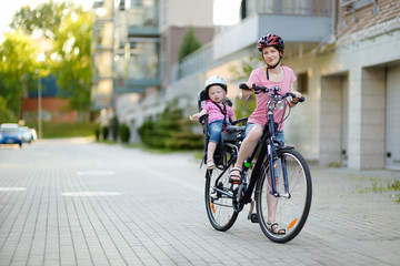 Young mother and her toddler girl riding a bicycle