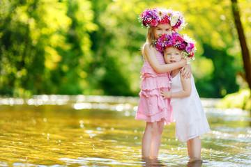 Two little sisters wearing flowers crowns
