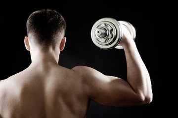 Young muscular sportsman with dumbbells on dark background