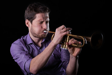 Handsome man playing on trumpet