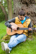 Man playing on guitar in forest