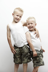 Portrait of two brothers hugging, and wearing camouflage pants
