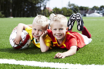 Portrait of two brothers on a football field
