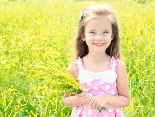 Adorable smiling little girl with yellow flowers on the meadow