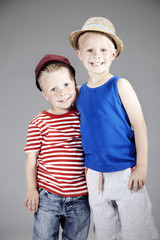 Portrait of two brothers hugging and wearing hats