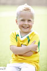 boy sitting on a football field wearing a football shirt