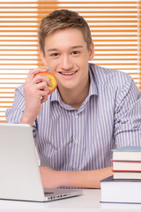 Smiling male student with stack of books.