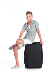 handsome guy sitting on luggage and smiling.