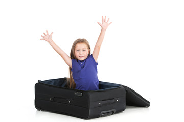 small girl sitting in black suitcase.