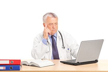 Mature doctor working on laptop at his desk