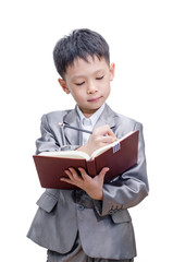 Little Asian boy in suit standing with a diary isolated over whi