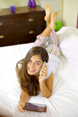 Young woman in bed talking on the phone with tablet