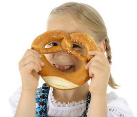Kind schaut durch Laugen-Brezel