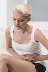 Woman having abdominal pain on sofa.