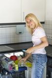 Frau räumt einen Spülmaschine ein