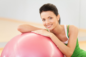 Woman sitting at gym with pilates ball.