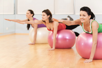 women working out in gym doing pilates.